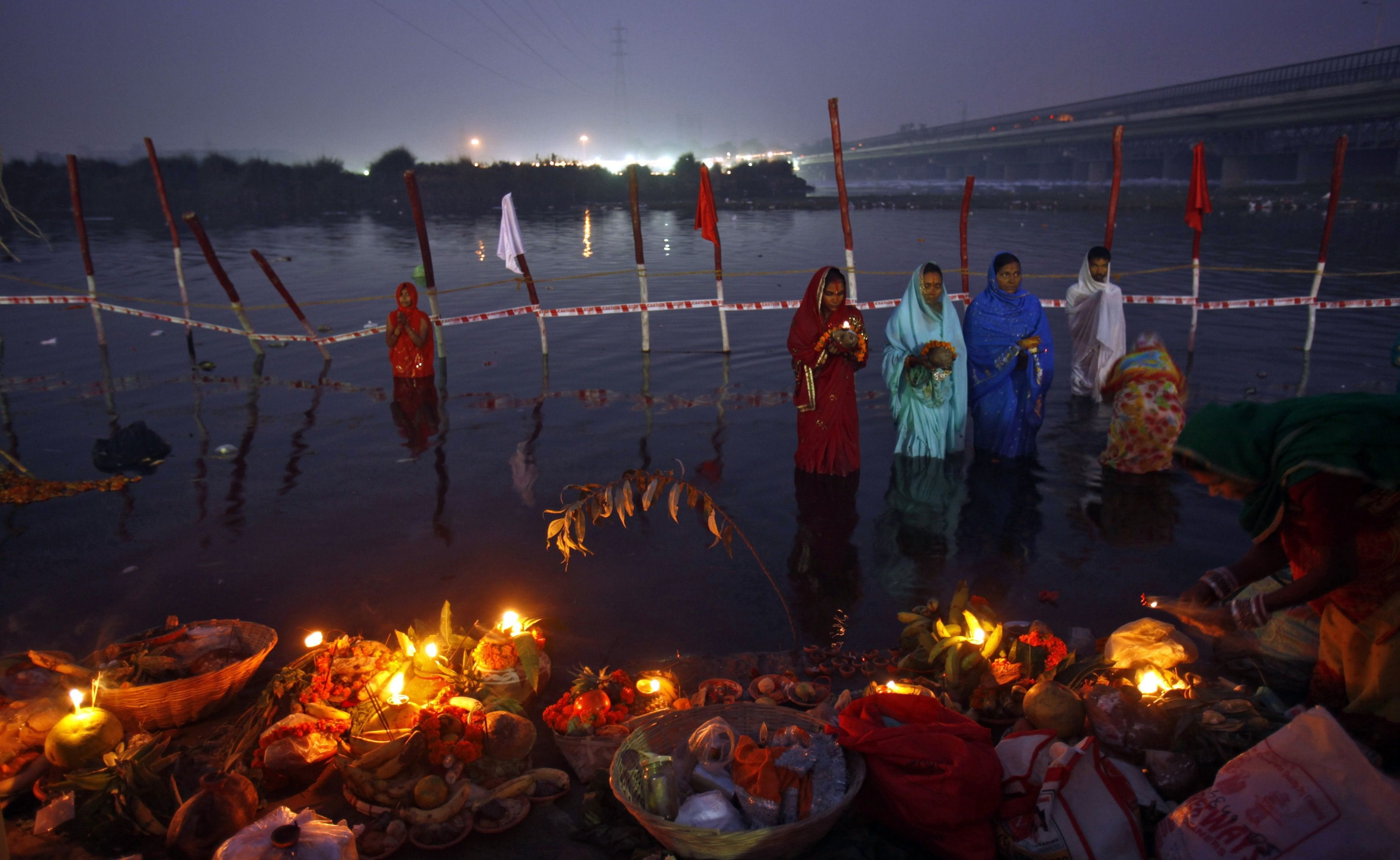 "Hindu devotees stand in the waters of river Yamuna to offer prayers to the Sun god during the Hindu religious festival ""Chhat Puja"" at dawn in New Delhi November 20, 2012. Hindu devotees worship the Sun god and fast all day for the betterment of their family and society during the festival. REUTERS/Mansi Thapliyal (INDIA - Tags: RELIGION SOCIETY TPX IMAGES OF THE DAY)"