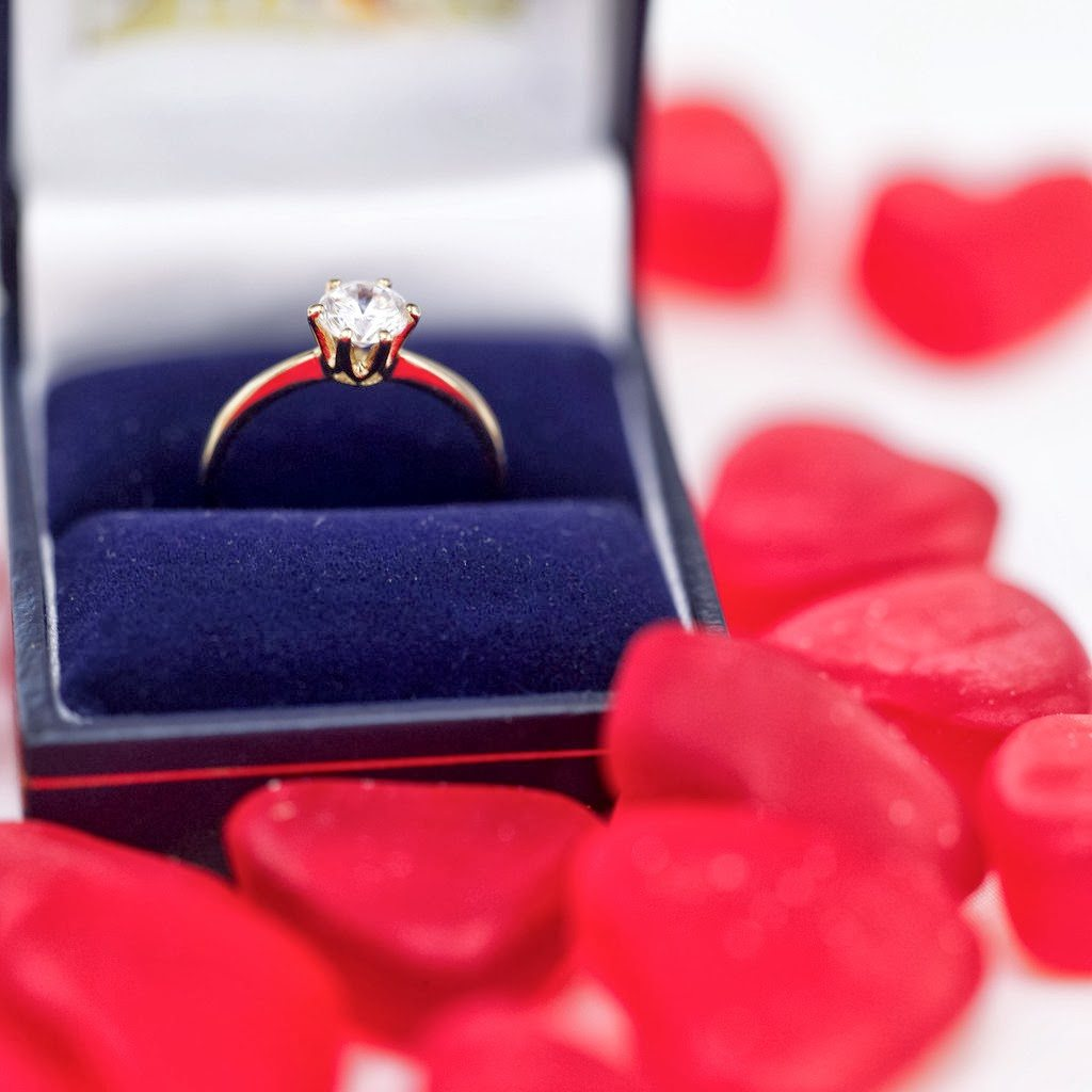 Red Heart Shaped Candies Surrounding an Engagement Ring in a Box --- Image by © Royalty-Free/Corbis