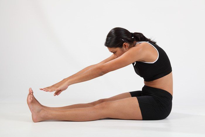Girl in hamstring stretch to touch toes