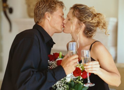 side view of a couple kissing holding champagne glasses